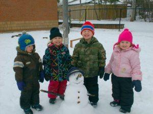 4 proud children next to snowman